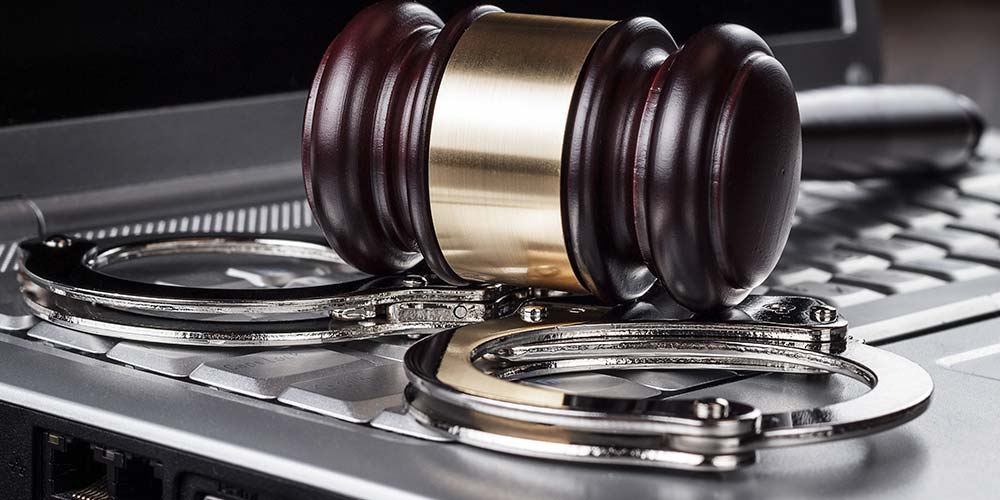 A gavel and handcuffs rest on a laptop keyboard, illustrating the concept of remote criminal proceedings during COVID-19 related social distancing