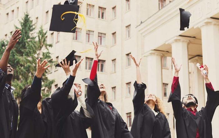 A group of law school graduates throw their caps in the air to celebrate their graduation