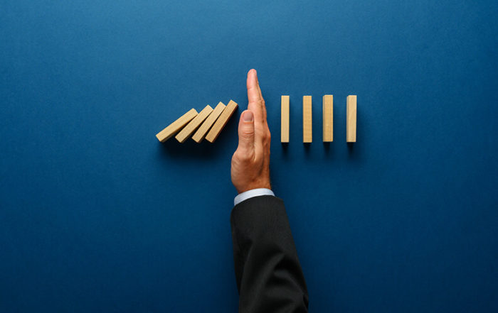 A hand separates two lines of dominos, keeping some from falling over and illustrating how crisis management tips for attorneys can help prevent additional damage.