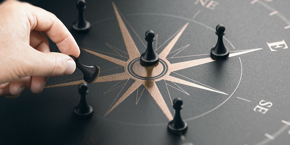 Chess pieces placed across the different points of a compass illustrates the change in direction occurring in legal companies in 2020.