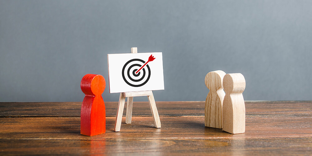 Concept art of wooden figures situated next to a red bullseye illustrates the kind of affordable targeted marketing law firms can use during the pandemic.