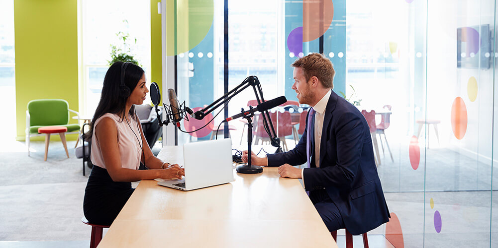 Interviewer converses with a guest while recording her popular legal podcast.