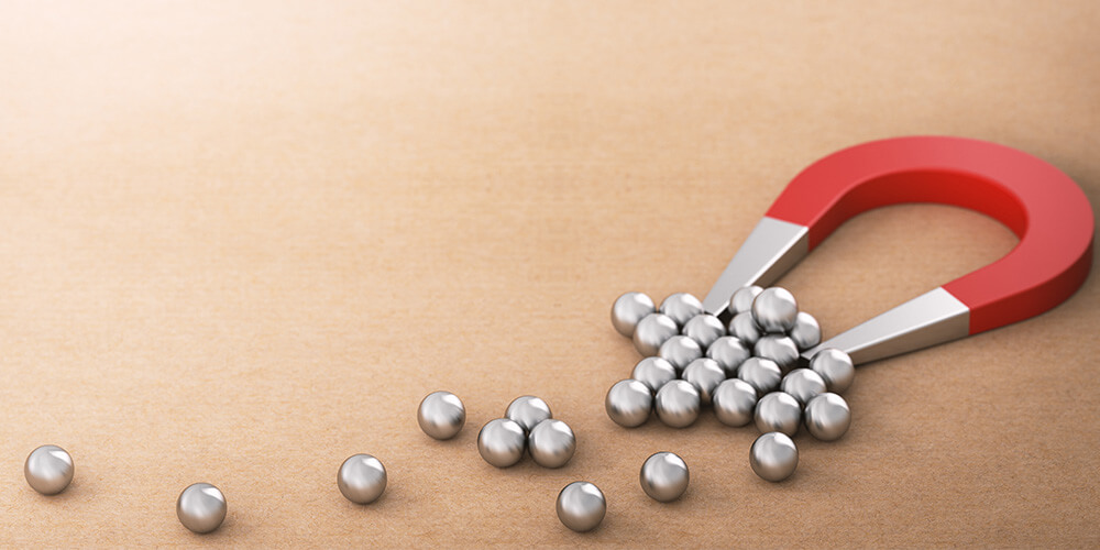 Photo of a magnet attracting metal marbles illustrates the concept of lead generation for lawyers.