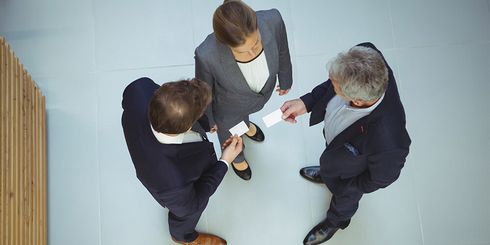 A trio of attorneys exchange business cards, which is a component of strong personal branding.