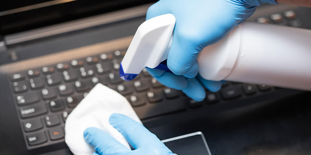 Photo of gloved hands cleaning a computer with disinfectant to avoid COVID-19, which reinforces the value of remote eDiscovery.