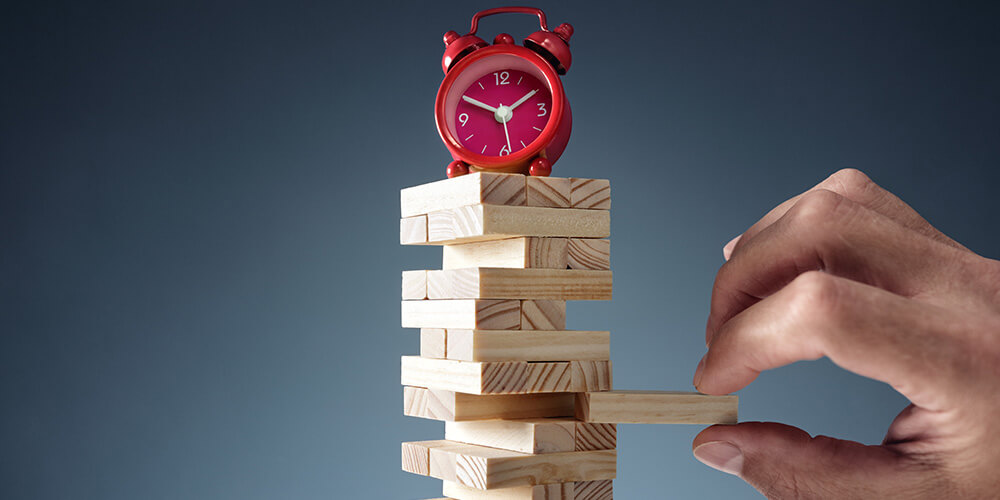 Photo of a hand removing a single block from a stack of Jenga tiles, while precariously balancing an alarm clock. This concept photo represents the balance of time and tricky discovery decisions.