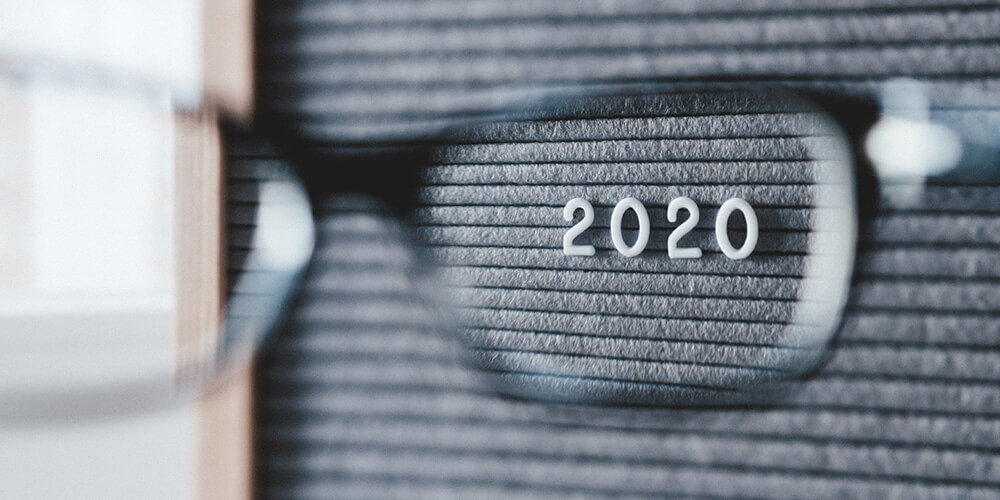 Photo of a letterboard taken through the lens of a pair of glasses, representing the act of eDiscovery. The year '2020' is in focus on the letterboard.