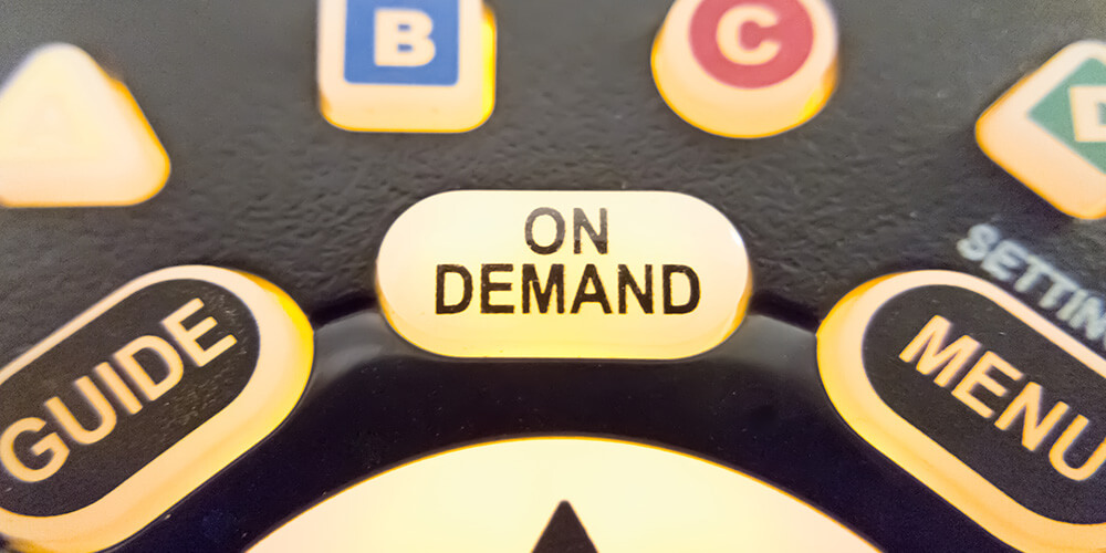 Photo of the 'On Demand' button of a television remote, which illustrates the ease and convenience of on-demand legal services.