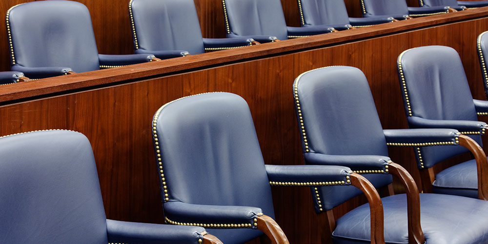 Photo of empty jury seats in a courtroom, illustrating the concept of voir dire for remote trials.