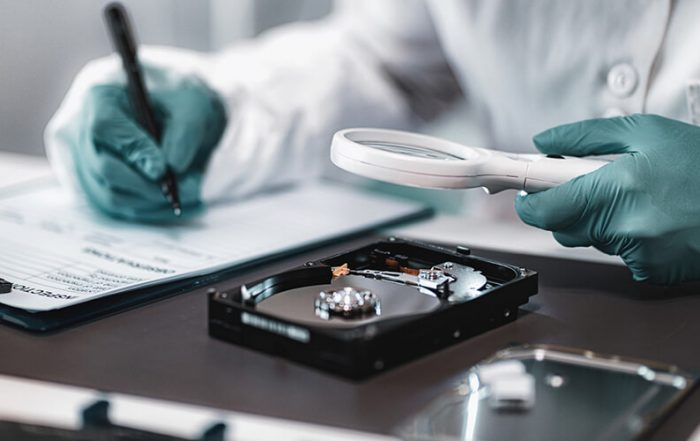 Photo of a forensic examiner inspecting a hard-drive and preparing a privileged forensic report.
