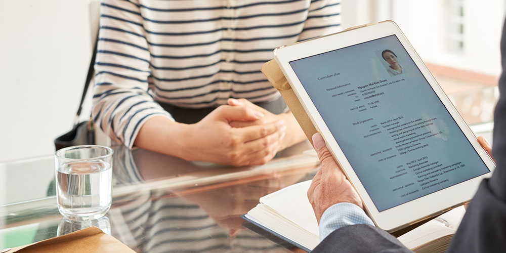 Photo of a prospective employer reading a lawyer's resume, which was not crafted using our legal resume writing tips.
