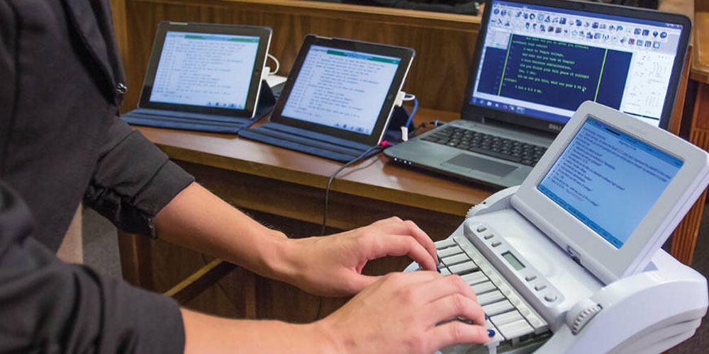 Photo of a court reporter actively recording the transcript of her case during her first court reporting assignment