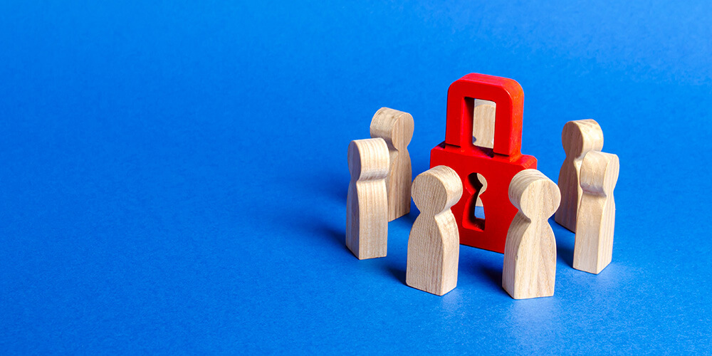 Photo of humanoid toy blocks surrounding a padlock, depicting the concept of protecting trade secrets during arbitration