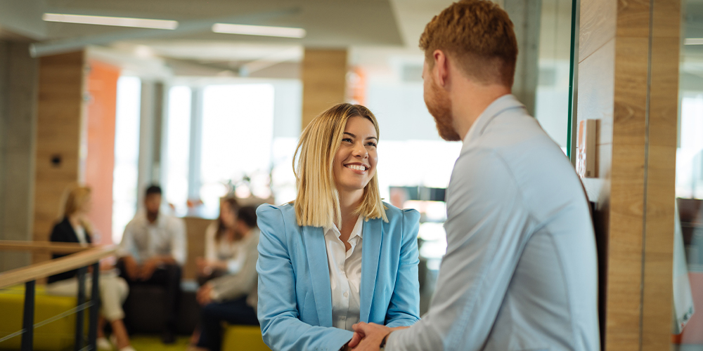 Young attorney shakes hands with her boss after landing her first law firm partnership.