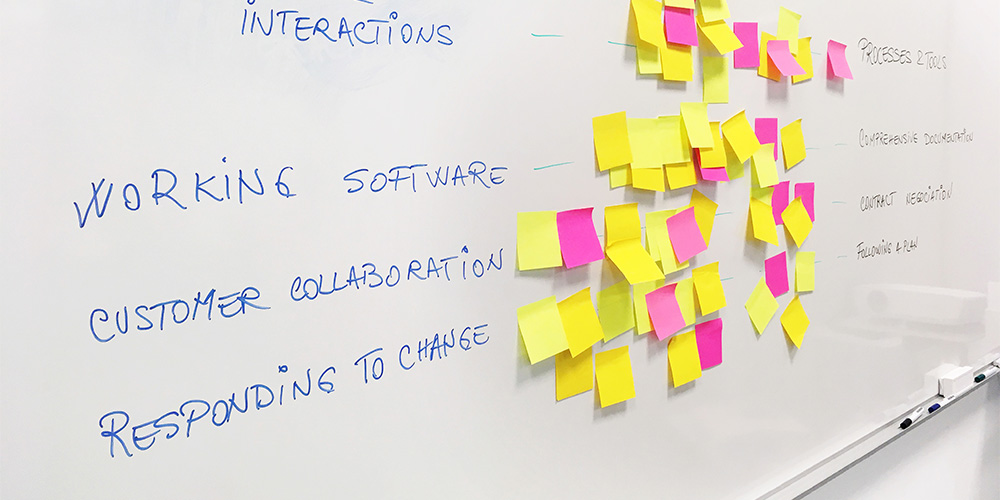 A white board and numerous sticky notes show how a law firm can work to improve the agility of their legal operations.